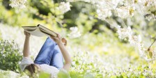 Woman reading book in grass under tree with white blossoms